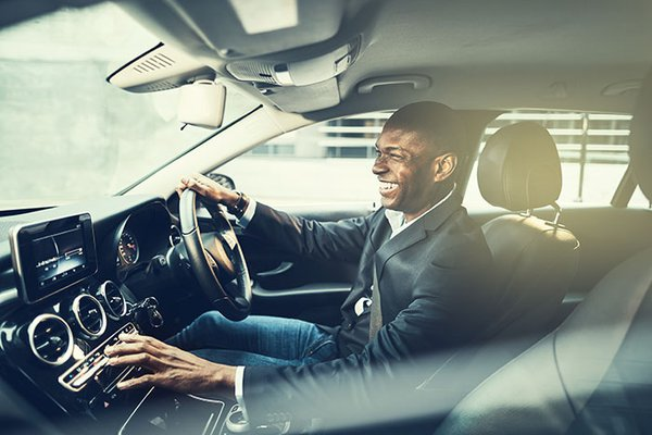 man driving luxury car laughing